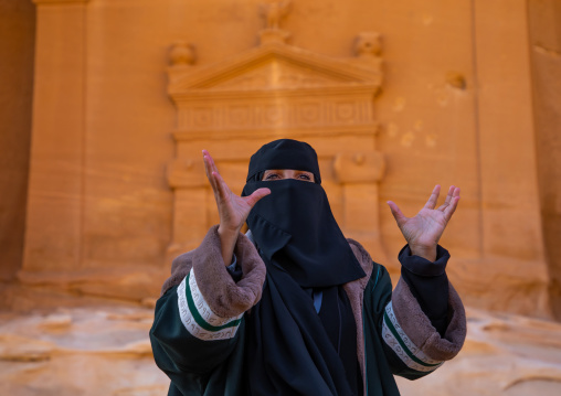 Saudi female guide in front of a tomb in al-Hijr archaeological site in Madain Saleh, Al Madinah Province, Alula, Saudi Arabia