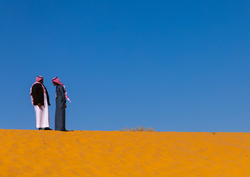 Saudi men on a sand dune, Al Madinah Province, Alula, Saudi Arabia