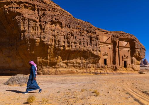 Saudi man walking in front of tombs in al-Hijr archaeological site in Madain Saleh, Al Madinah Province, Alula, Saudi Arabia