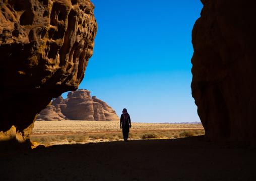 Sausi man walking in the middle of the mountains of wadi al gura, Al Madinah Province, Alula, Saudi Arabia
