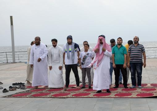 Saudi men praying on the beach, Mecca province, Jeddah, Saudi Arabia