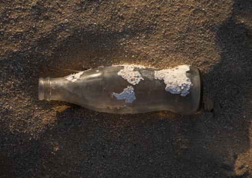 Coca Cola bottle with shell on it on a beach, Red Sea, Farasan, Saudi Arabia