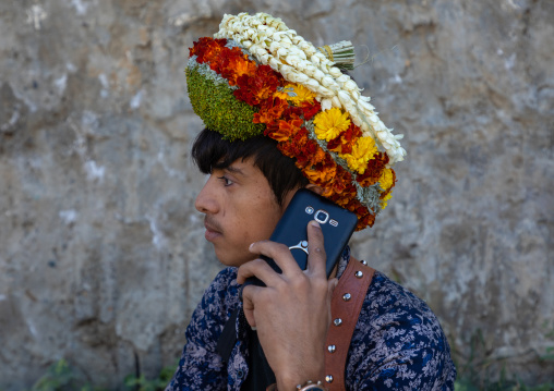 Portrait of a flower young man calling on his mobile phone and wearing a floral crown on the head, Jizan Province, Addayer, Saudi Arabia