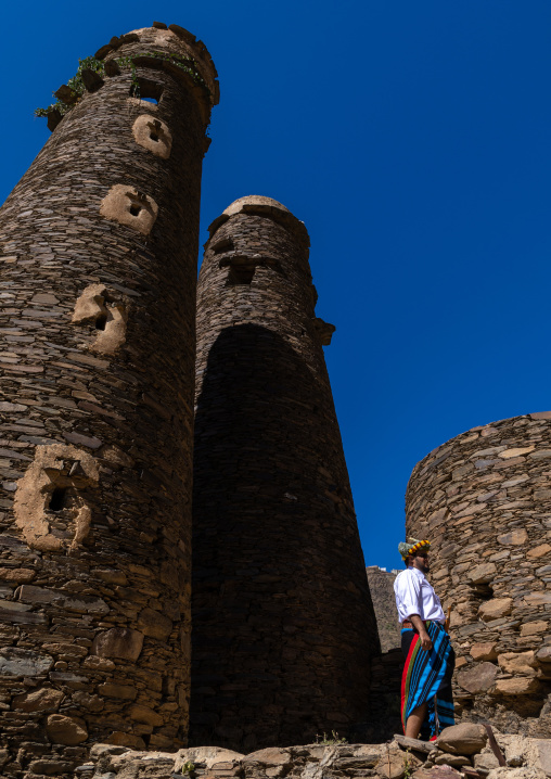 Portrait of a flower man wearing a floral crown on the head near a stone watchtower, Jizan Province, Addayer, Saudi Arabia