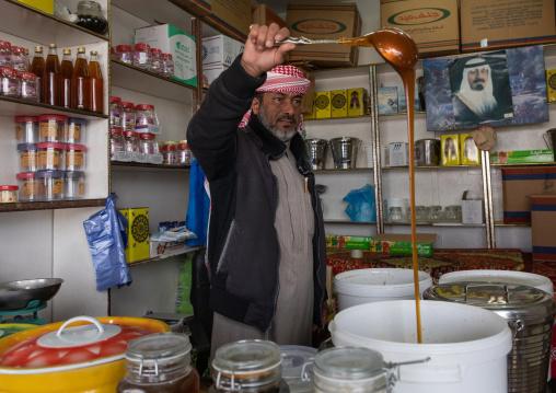 Saudi man selling honey in a shop, Asir province, Abha, Saudi Arabia