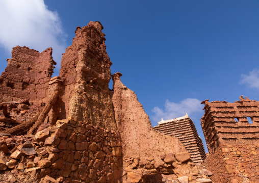 Red stone and mud collpased house in a village, Asir province, Sarat Abidah, Saudi Arabia