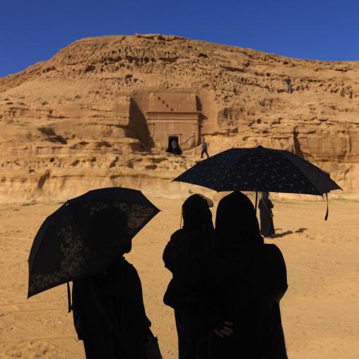 Tourists with umbrellas in madain saleh archaeologic site, Al Madinah Province, Alula, Saudi Arabia