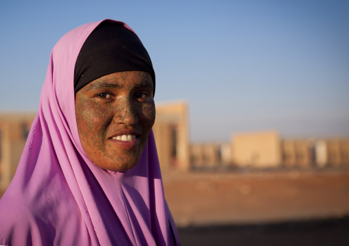 Young woman with qasil on her face posing in front of the ruins of burao technology institute, Burao, Somaliland