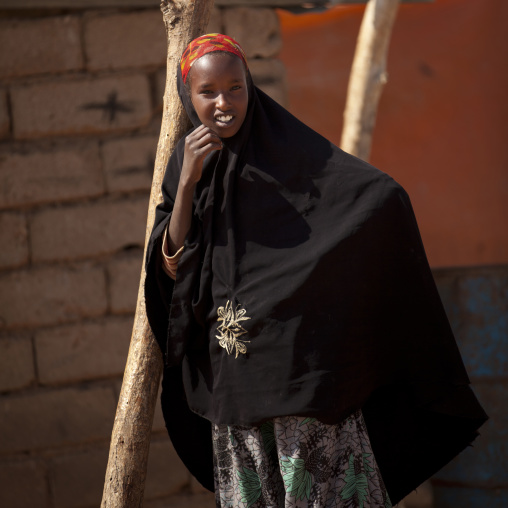 Portrait of a smiling teenage girl leaning against a tree, Burao, Somaliland
