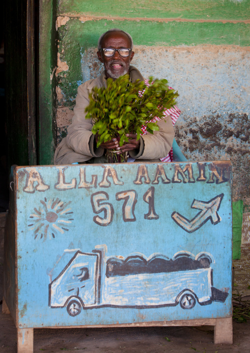A Senior Khat Seller Standing Outside A House In Front Of A Painted Sign, Baligubadle, Somaliland