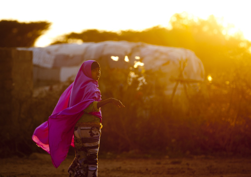 A woman wearing a pink hijab floating in the wing at sunset, Baligubadle, Somaliland