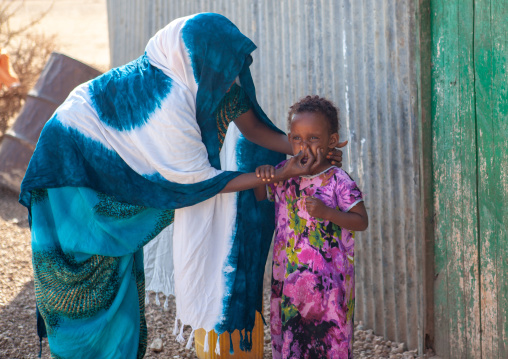 Somali mother washing the face of her daughter outside of their house, Woqooyi galbeed province, Baligubadle, Somaliland