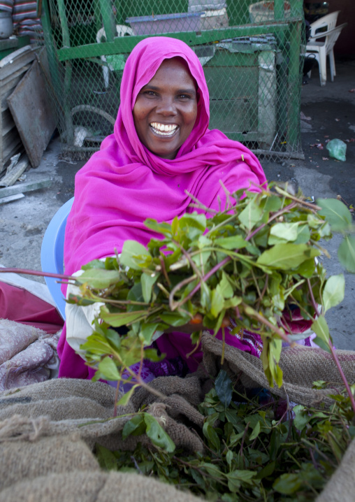 A woman wearing a bright pink hijab selling khat on the street, Boorama, Somaliland