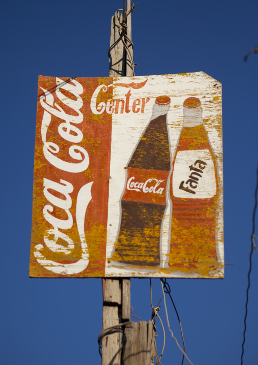 Coca cola  and fanta painted advertisement stuck to a wooden pillar, Boorama, Somaliland