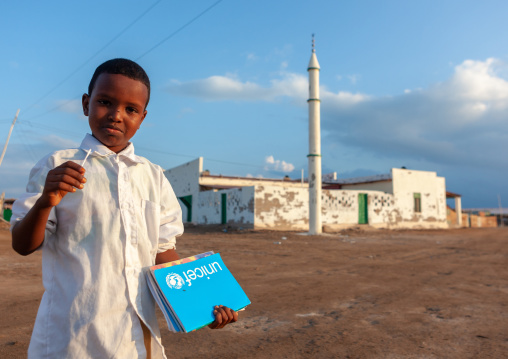 Somali boy with a unicef blue book in front of a mosque, Awdal region, Zeila, Somaliland