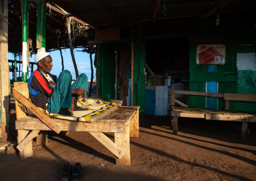 Somali man resting on a bed in a bar, Awdal region, Zeila, Somaliland