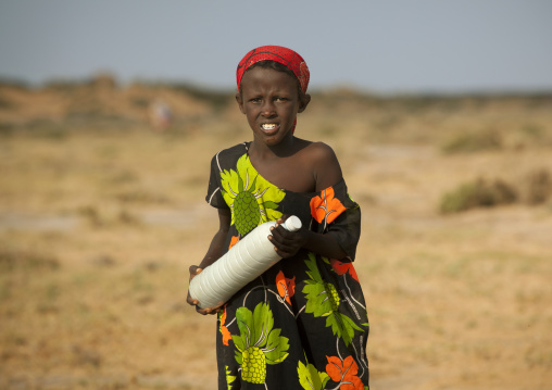 A nomad woman carrying a bottle of camel milk in the desert, Berbera area, Somaliland