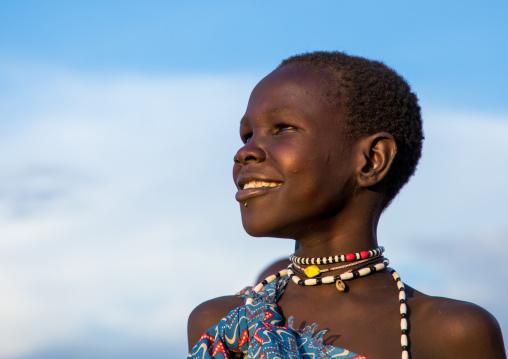 Portrait of a smiling Toposa girl looking away, Namorunyang State, Kapoeta, South Sudan