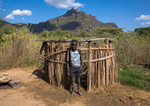 Larim tribe boy in front of a house designed for the children, Boya Mountains, Imatong, South Sudan