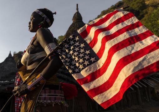 Larim tribe woman with an american flag during a wedding celebration, Boya Mountains, Imatong, South Sudan