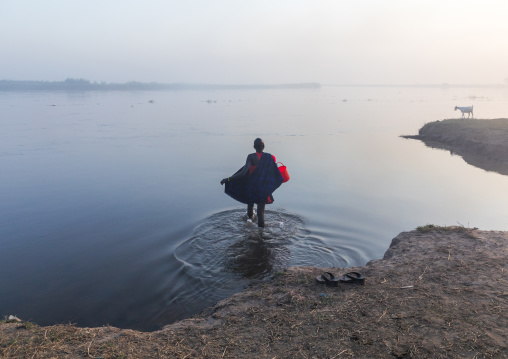 Mundari tribe woman collecting water in the river Nile, Central Equatoria, Terekeka, South Sudan