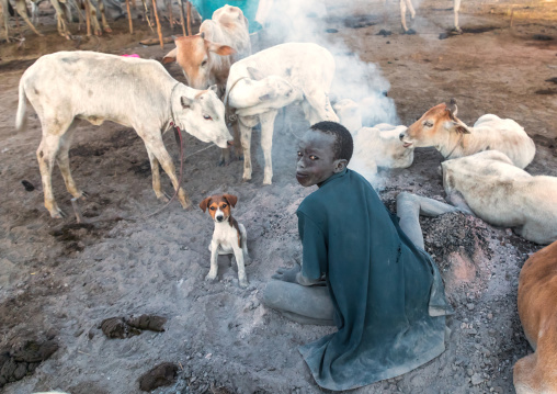 Mundari tribe boy making a campfire made with dried cow dungs to repel flies and mosquitoes, Central Equatoria, Terekeka, South Sudan