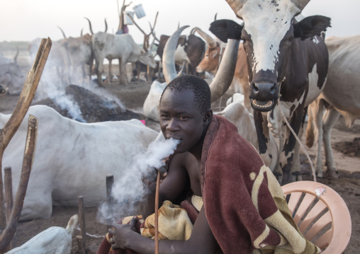 Mundari tribe man smoking shisha in a cattle camp, Central Equatoria, Terekeka, South Sudan