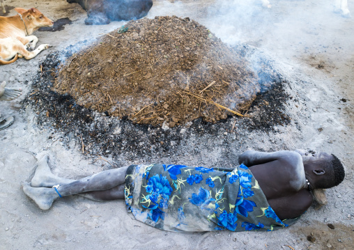 Mundari tribe man resting on a wooden pillow in front of a bonfire made with dried cow dungs to repel mosquitoes, Central Equatoria, Terekeka, South Sudan