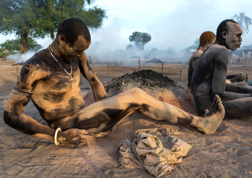 Mundari tribe men covering their bodies in ash to protect from the mosquitoes and flies bites, Central Equatoria, Terekeka, South Sudan