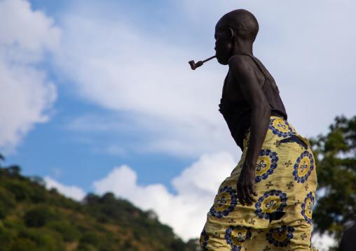 Lotuko trive woman smoking a pipe, Central Equatoria, Illeu, South Sudan