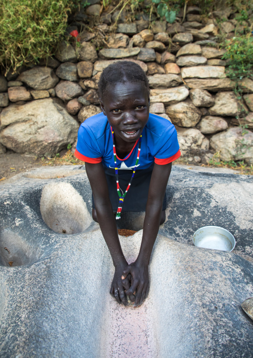 Lotuko tribe woman grinding grains in a hole in the rock, Central Equatoria, Illeu, South Sudan