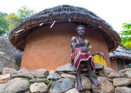 Woman sit in front of a Lotuko tribe thatched house, Central Equatoria, Illeu, South Sudan