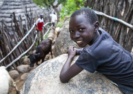 Boy looking at cows in a small alley of a Lotuko village, Central Equatoria, Illeu, South Sudan