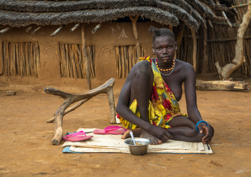 Portrait of a Larim tribe woman eating in front of her house, Boya Mountains, Imatong, South Sudan