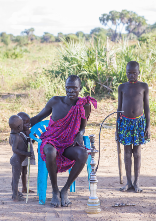 Mundari tribe father with his children smoking shisha, Central Equatoria, Terekeka, South Sudan