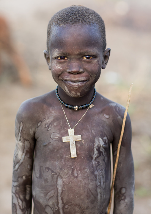 Mundari tribe boy with a christian cross covered in ash to protect from the mosquitoes and flies, Central Equatoria, Terekeka, South Sudan