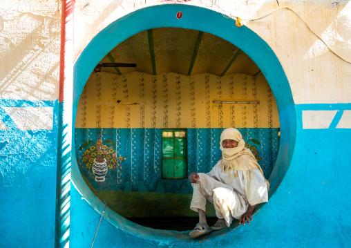 Sudanese boy resting inside a circular window in a restaurant, Khartoum State, Khartoum, Sudan