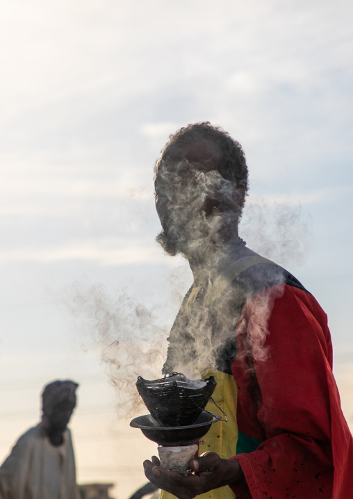 Man with insence burning during the friday sufi celebration at sheikh Hamad el Nil tomb, Khartoum State, Omdurman, Sudan