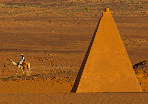 Sudanese man and his camel in front of the pyramids of the kushite rulers at Meroe, Northern State, Meroe, Sudan