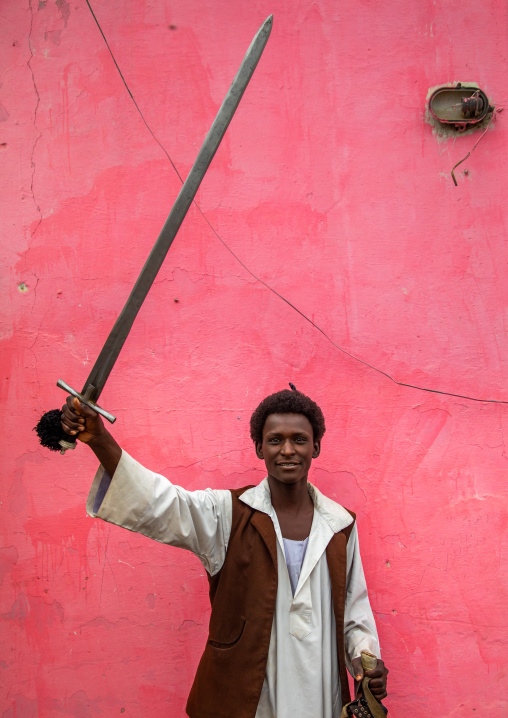 Beja tribe warrior with his sword in front of a pink wall, Red Sea State, Port Sudan, Sudan
