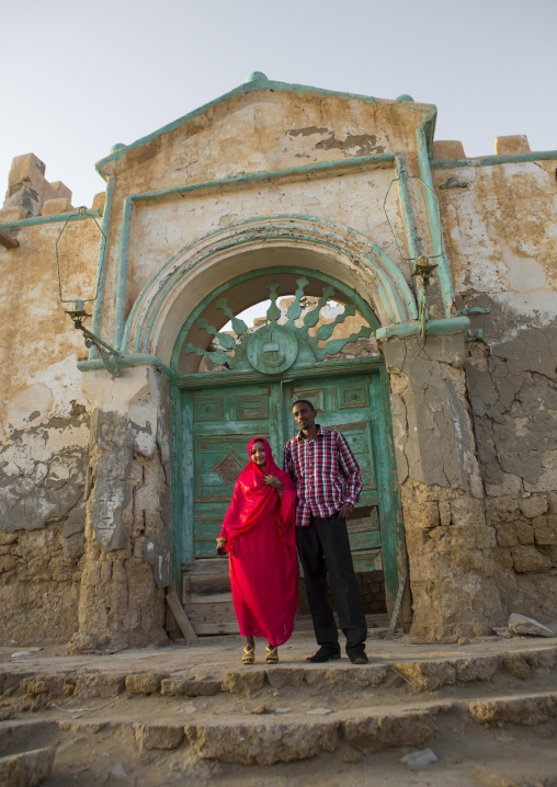 Sudan, Port Sudan, Suakin, couple in front of a huge green door of a ruined ottoman coral buildings