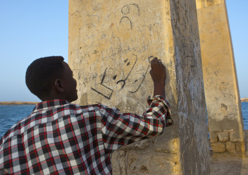 Sudan, Port Sudan, Suakin, man writing on the wall of a ruined ottoman coral buildings