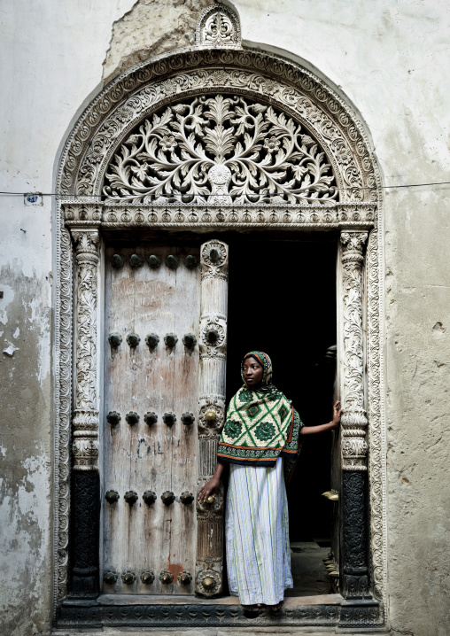 Swahili girl standing in front of  an old door in stone town zanzibar, Tanzania