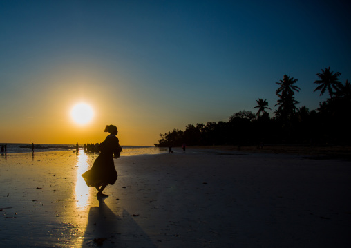 Tanzania, Zanzibar, Kizimkazi, girl running on beach during sunset