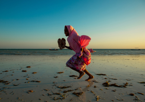 Tanzania, Zanzibar, Kizimkazi, young muslim girl in school uniform running on beach
