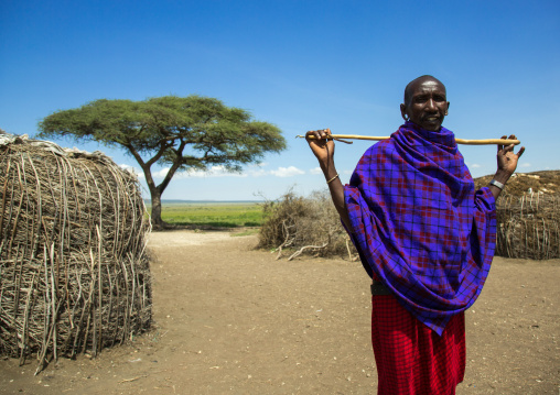 Tanzania, Ashura region, Ngorongoro Conservation Area, maasai man with a stick outside his home