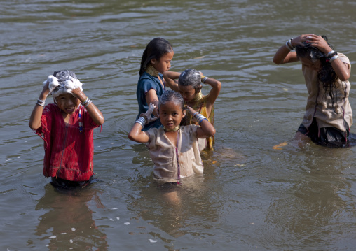 Long neck children having bath in river in nam peang din village, North thailand