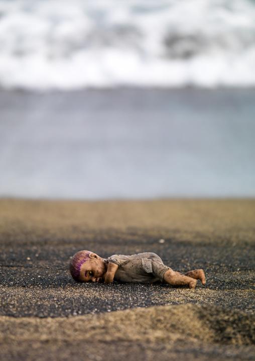 Doll lying on black sandy beach at waterside, Shefa Province, Efate island, Vanuatu