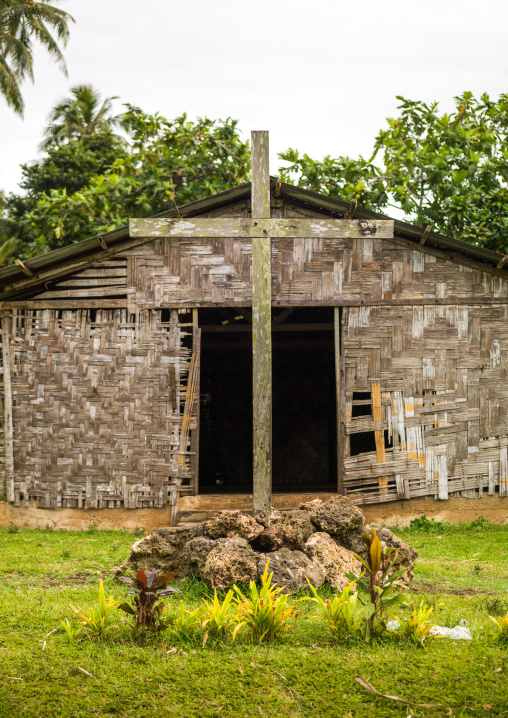 Tomb with a cross in front of a traditional house made with palm leaves, Malampa Province, Malekula Island, Vanuatu