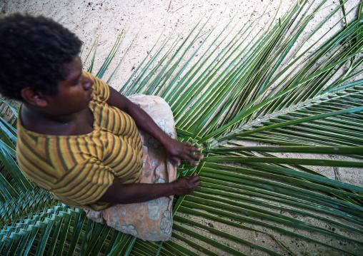 Ni-Vanuatu woman weaving a palm leaf to make a roof, Malekula island, Gortiengser, Vanuatu